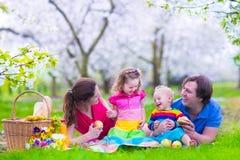 Ung familj med ungar som har picknicken utomhus Royaltyfri Foto