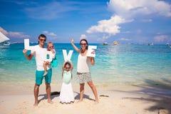 Ung familj och två ungar med ordet FÖRÄLSKELSE på Royaltyfri Foto