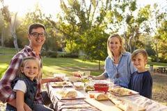 Ung familj på en picknick i en tabell i en parkerablick till kameran Royaltyfri Foto