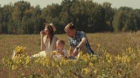 Ung familj på en picknick i fältet arkivfilmer