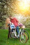 Ung familj på en trädgård för cyklar på våren Arkivbild