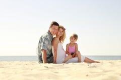 Ung familj på stranden Arkivbilder