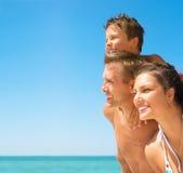 Ung familj på stranden Fotografering för Bildbyråer