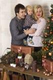 Ung familj som beundrar en julgran och gåvor Arkivbilder
