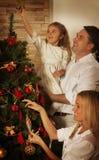 Ung familj som dekorerar julgranen Arkivbilder