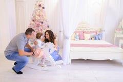Ung familj som förbereder sig för kommande i rymligt sovrumljus på Fotografering för Bildbyråer