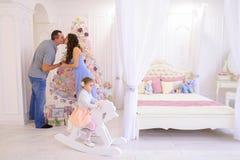Ung familj som förbereder sig för kommande i rymligt sovrumljus på Arkivbild