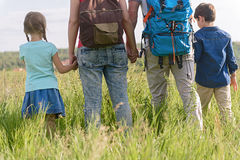 Ung familj som fotvandrar på berget royaltyfria foton