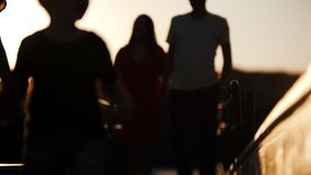 Ung familj som går på bron mot den härliga solnedgången Barnen som framåt körs Föräldrar som bakom följer lager videofilmer