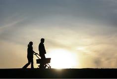 Ung familj som går på solnedgång Fotografering för Bildbyråer