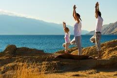 Ung familj som gör yogaövning på stranden Royaltyfria Bilder