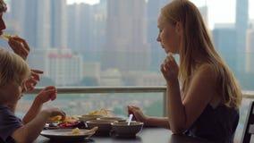 Ung familj som har en frukost, lunch på deras balkong i en skyskrapa med en sikt på ett helt centrum av staden stock video