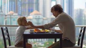 Ung familj som har en frukost, lunch på deras balkong i en skyskrapa med en sikt på ett helt centrum av staden arkivfilmer