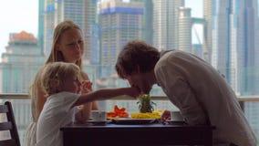 Ung familj som har en frukost, lunch på deras balkong i en skyskrapa med en sikt på ett helt centrum av staden lager videofilmer