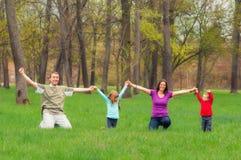 Ung familj som har gyckel i skogen Fotografering för Bildbyråer