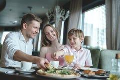 Ung familj som har lunch arkivfoton