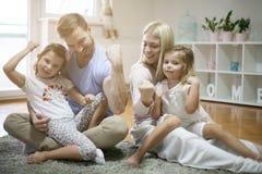 Ung familj som hemma spelar royaltyfri bild