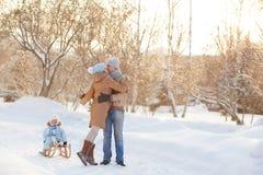 Ung familj som kramar i parkera Fotografering för Bildbyråer