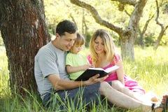 Ung familj som läser bibeln Royaltyfria Bilder