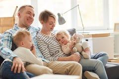 Ung familj som omfamnar sig på soffan royaltyfria foton