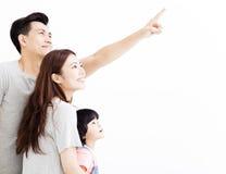 Ung familj som pekar och ser upp Royaltyfria Bilder