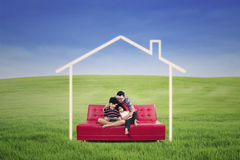 Ung familj som placeras på en soffa som drömmer ett hem i naturen royaltyfri fotografi