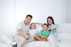 Ung familj som poserar på soffan Royaltyfri Fotografi
