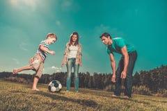 Ung familj som spelar fotboll Royaltyfri Foto