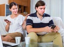 Ung familj som spelar med telefonapparater Royaltyfri Foto