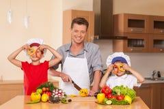 Ung familj som tillsammans förbereder sallad Royaltyfria Foton