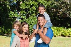 Ung familj som tillsammans står Arkivfoton