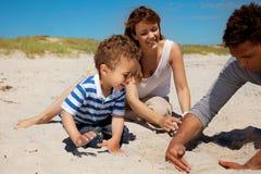 Ung familj som tycker om sommar på en strand Arkivfoto