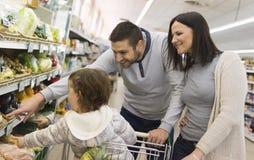 Ung familjköpande i supermarket arkivbild