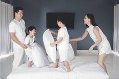 Ung familjlek med kuddar i sovrummet Arkivbild