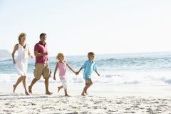 Ung familjspring längs Sandy Beach On Holiday Royaltyfria Bilder