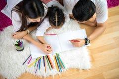Ung familjteckning samman med färgrika blyertspennor hemma royaltyfri bild
