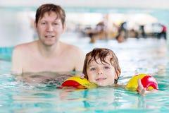 Ung farsa som undervisar hans lilla son att simma inomhus Arkivfoton