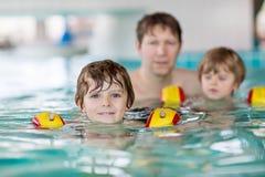 Ung farsa som undervisar hans två lilla söner att simma inomhus Royaltyfri Fotografi