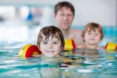 Ung farsa som undervisar hans två lilla söner att simma inomhus Arkivbild