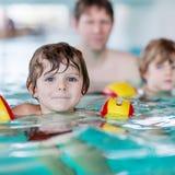 Ung farsa som undervisar hans två lilla söner att simma inomhus Arkivbilder