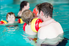 Ung farsa som undervisar hans två lilla söner att simma inomhus Fotografering för Bildbyråer