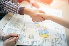 Ung fastighet för egenskap för hyra för familjparköp Medel som ger konsultation till mannen och kvinnan Undertecknande avtal royaltyfri foto