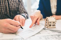 Ung fastighet för egenskap för hyra för familjparköp Medel som ger konsultation till mannen och kvinnan Undertecknande avtal royaltyfria foton