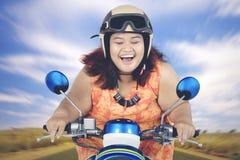 Ung fet kvinna som rider en sparkcykel Arkivfoton