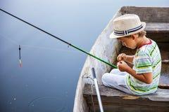 Ung fiskare som fångar fisken på fisk-stången Royaltyfri Foto