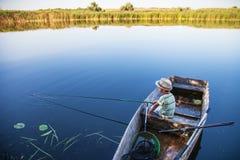 Ung fiskare som fångar fisken på fisk-stången Arkivbilder