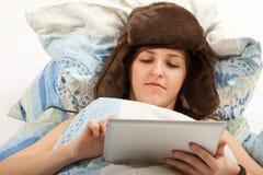 Flickan är att ligga som är sjukt i säng, och att se in i henne tableten Arkivbild