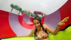 Ung flicka för blandat lopp som har den roliga vattenglidbanan i Waterpark 4K thailand arkivfilmer
