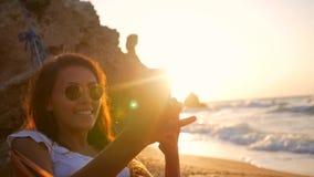 Ung flicka för blandat lopp som tar det Selfie fotoet, medan koppla av i hängmatta på stranden under fantastisk solnedgång Slowmo stock video