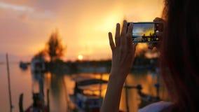 Ung flicka för blandat lopp som tar fotoet av den härliga solnedgången genom att använda mobiltelefonen på den Fishermans pir Slo stock video